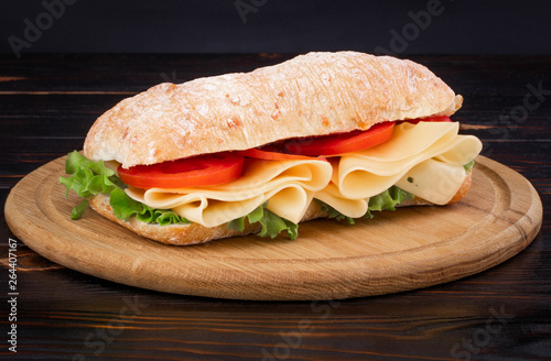Foto op Canvas Snack Ciabatta sandwich with lettuce , prosciutto and cheese on wooden board