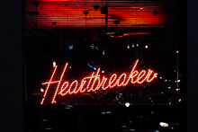 A Red Neon Sign Displaying The Words 'Heartbreaker' Is Glowing Behind Window Blinds