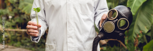 Valokuva  cropped view of scientist in white coat holding rubber gas mask and flask with p