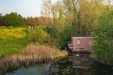 Houseboat hidden between bushes in springtime. - 264426168