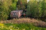 Houseboat hidden between bushes in springtime. - 264426196
