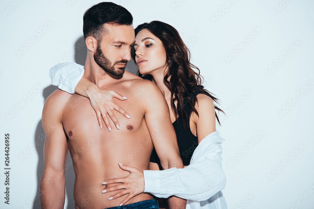 Fototapety, obrazy: girlfriend in white shirt embracing with boyfriend on grey