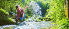 Happy Young Woman Smiling And Touching Water In Rapid River