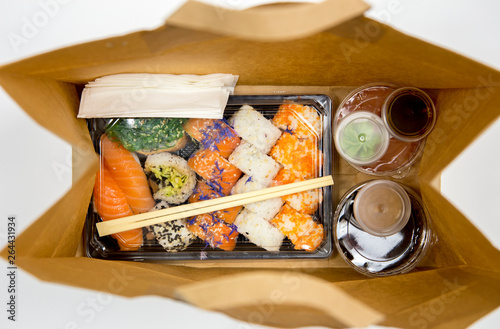 Fototapeta Sushi to go concept. Top view of takeaway box with sushi rolls and various sauce cups in brown paper bag. obraz