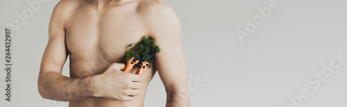 Panoramic shot of shirtless man cutting plant on armpit with secateurs isolated Wallpaper Mural
