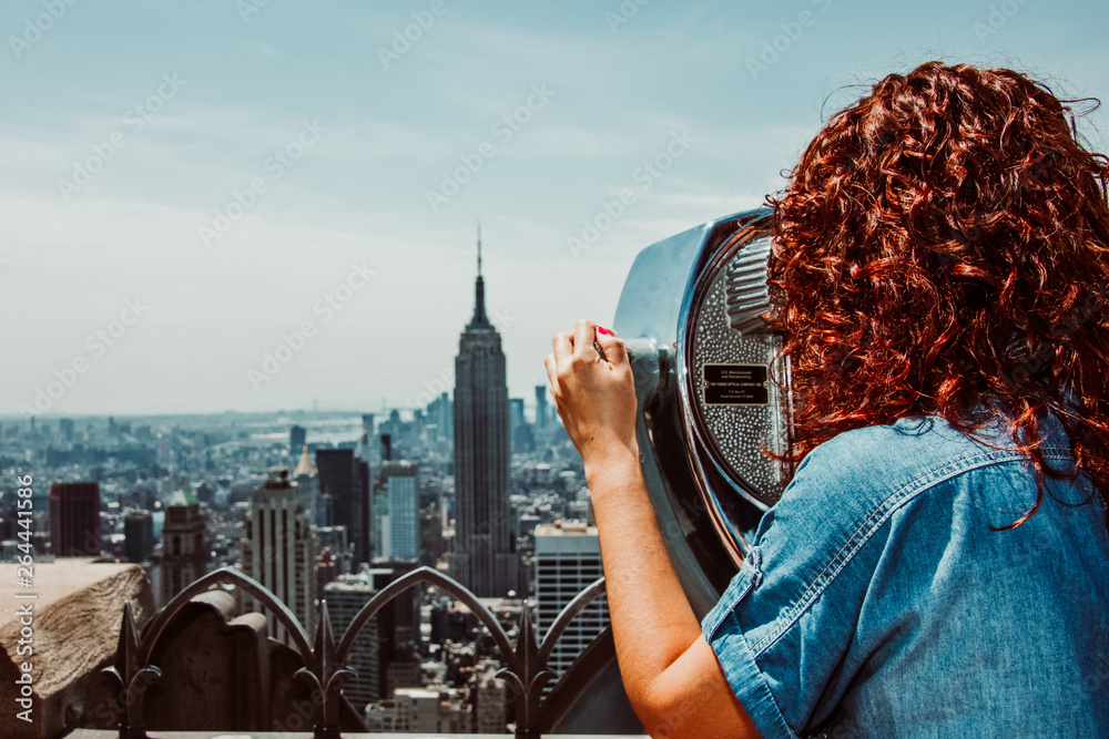 Fototapeta Young woman enjoying the New York skyline from high skyscrape in the morning. Travel photography