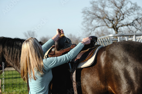Girl with horse putting on saddle to go horseback riding.