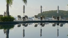 Hand Held Shot Of Tranquil Pool Area With Sun Beds And Tables Around A Pool With Ocean And Tropical Jungle Mountains In The Background, No People, No Wind, Perfect Reflections, Good Copyspace