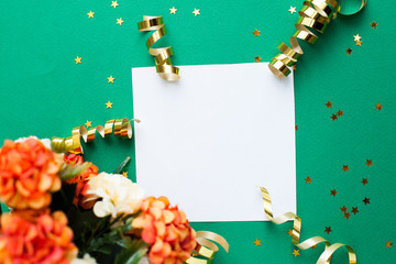 White paper sheet, golden decorations and sparkles on green background