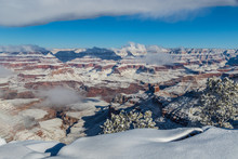 Grand Canyon In Winter, Viewed From The South Rim. Snow Covers The Canyon Walls. Clouds Clinging To The Canyon, And Overhead In The Blue Sky. Edge Of The Rim Rim And Bushes Covered With Snow.