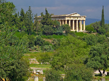 Temple Of Hephaestus In Athens, Greece. Landscape With Olive And Other Trees Cloudy Sky, Bright Light, And Ancient Greek Temple.