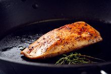 Roasted Turkey Breast With A Golden Crust And Seasonings On A Black Pan.