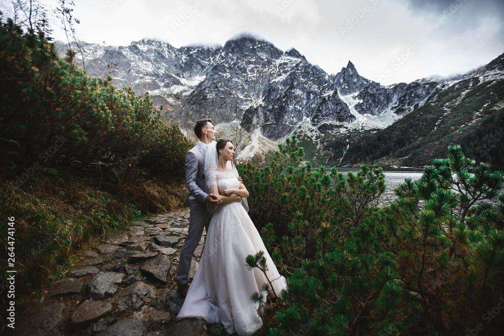 Fototapety, obrazy: Wedding couple walking near the lake in Tatra mountains in Poland. Morskie Oko. Beautiful summer day