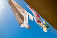 Clothes Hanging In The Sun On The Balcony Of A House, In The Blue Sky. Low Angle View, Backlit, With Glow And Flare. Sheet, Tablecloth And Towel Waving In The Wind.