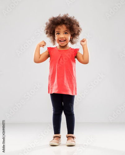Fotografía  childhood and people concept - happy little african american girl showing her po