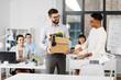 business, new job and corporate concept - male office worker with box of personal stuff and happy smiling colleague introducing workplace
