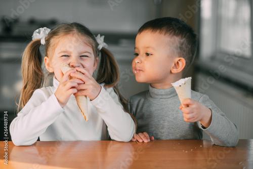 Fototapeta kids boy and girl eating ice cream cone in the kitchen is a lot of fun obraz na płótnie