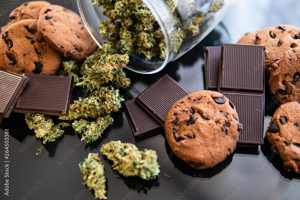 Fototapeta Treatment of medical marijuana for use in food, black background. Concept of Cookies and chocolate with cannabis herb CBD. Chocolate and Cookies with cannabis and buds of marijuana on the table.