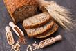 Leinwandbild Motiv Loaf of wholegrain bread for breakfast, ingredients for baking and ears of rye or wheat grain