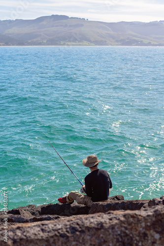 Foto auf Gartenposter Sansibar Young Male Fishing From Breakwater Rocks At A Marina