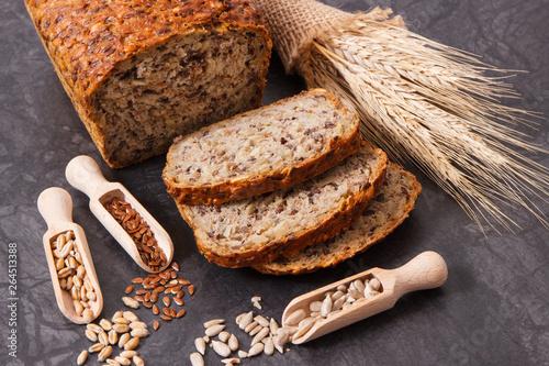 Loaf of wholegrain bread for breakfast, ingredients for baking and ears of rye o Fototapet