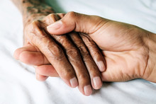 Hands Of An Old Man With Wrinkled And Wrinkles On A White Bed In A Hospital.