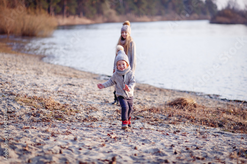 Aluminium Prints Cathedral Cove A boy and a girl having fun outside in early spring in the forest near the water. A sister and brothe together. Friendship and family concept