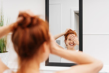 Laughing Young Woman Looking At Herself In Mirror