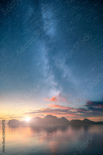 Fototapeta Beautiful vertical view of an ocean and mountains with epic milky way on the sky and star trail effect. obraz