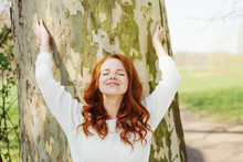 Blissful Young Redhead Woman Hugging A Tree