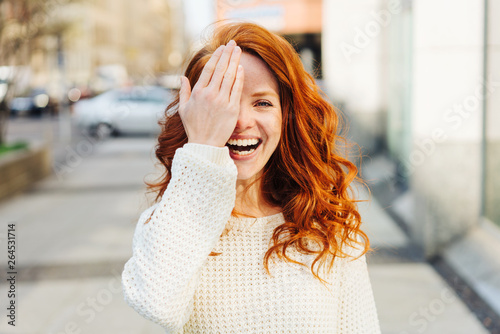 Photo  Laughing playful young woman covering one eye