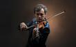 Leinwandbild Motiv Lonely violinist composing on cello with nothing around