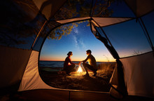 View From Inside Tourist Tent. Young Romantic Couple, Man And Woman Sitting At Campfire Holding Hands On Sea Shore On Evening Starry Sky At Sunset And Sea Water Background. Tourism And Love Concept.