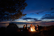Night Summer Camping On Lake Shore. Group Of Five Young Happy Tourists Sitting In High Grass Around Bonfire Near Tent Under Beautiful Blue Evening Sky. Tourism, Friendship And Beauty Of Nature Concept