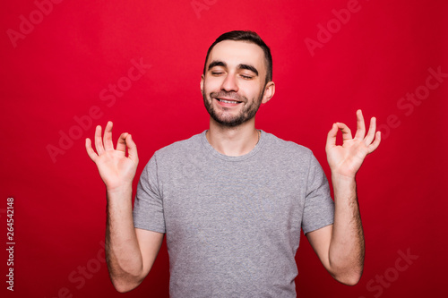 Valokuva  Portrait of a cheerful young man showing okay gesture isolated on the red backgr