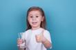 Leinwandbild Motiv Cute little girl drinking water from glass on blue background
