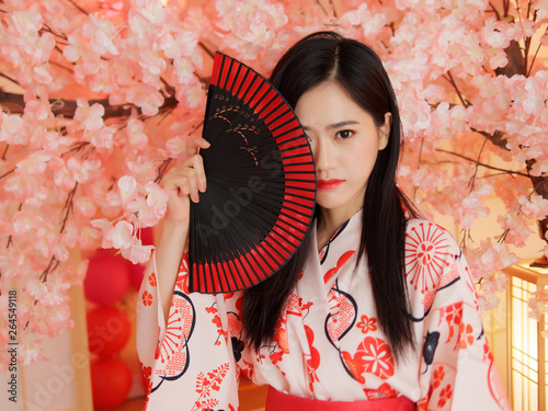 Portrait of attractive Chinese woman wearing traditional Japanese Kimono, smiling at camera, oriental beauty Fototapet