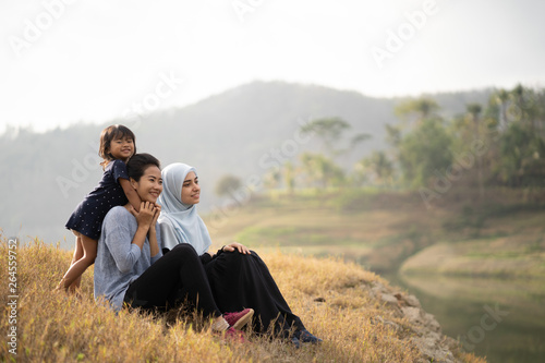Fotografie, Obraz  happy young muslim woman friend and daughter enjoying outdoor together sitting o