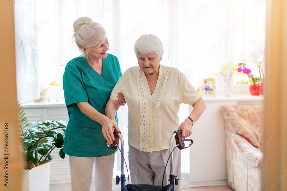 Fototapety, obrazy: Nursing assistant helping senior woman with walking frame