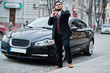 Stylish indian businessman in formal wear with mobile phone standing against black business car on street of city. Speak on cellphone and looking at his watches.