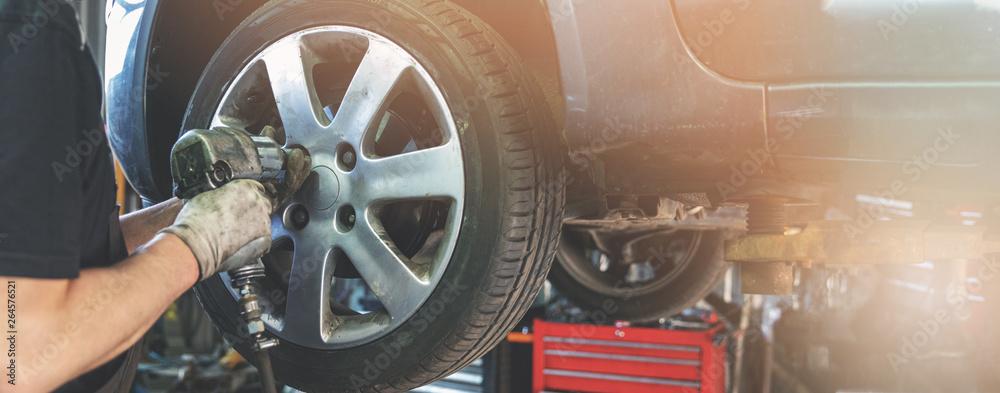 Fototapety, obrazy: car mechanic screwing the wheel at auto repair garage