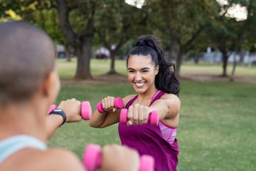 Happy women training with dumbbells