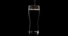 Dark Beer Closeup. Pint Of Cold Craft Beer Isolated On Black Background