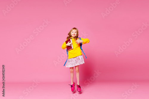 Back to school. Happy blonde baby girl jumps and holds a book and a red Apple in her hands on a pink background.   Education and intellectual development of children. World book day. - 264582349