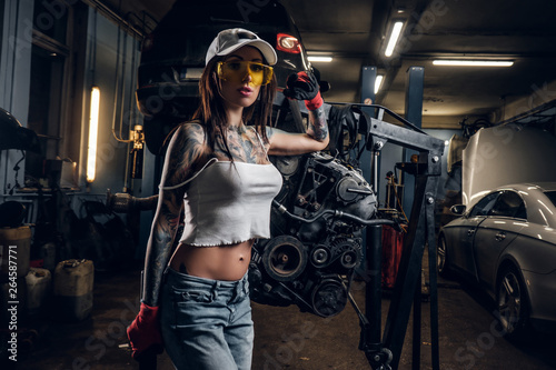 Fototapeta  Sexual tattoed girl wearing cap and dirty clothes posing next to a car engine su