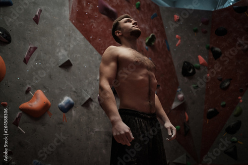 Photo  Athletic man stretching before climbing in a bouldering gym