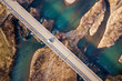 Aerial view of white bridge with moving car over blue water and stony islands.