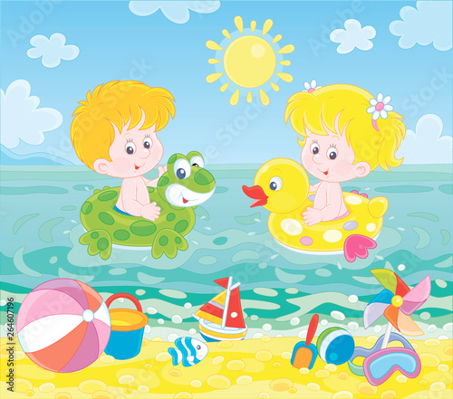 Happy little kids swimming in inflatable rings in blue water on a sea beach on a sunny summer day, vector illustration in a cartoon style