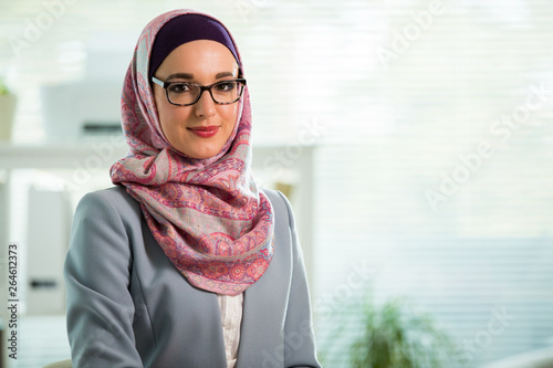 Fotografia Beautiful young working woman in hijab, suit and eyeglasses standing in office, smiling