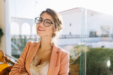 Closeup Portrait Of Young Woman Wearing Stylish Glasses, Smart Lady In Elegent Pink Jacket With Beige Blouse, Cute Student. Big Window With Nice View On Background.